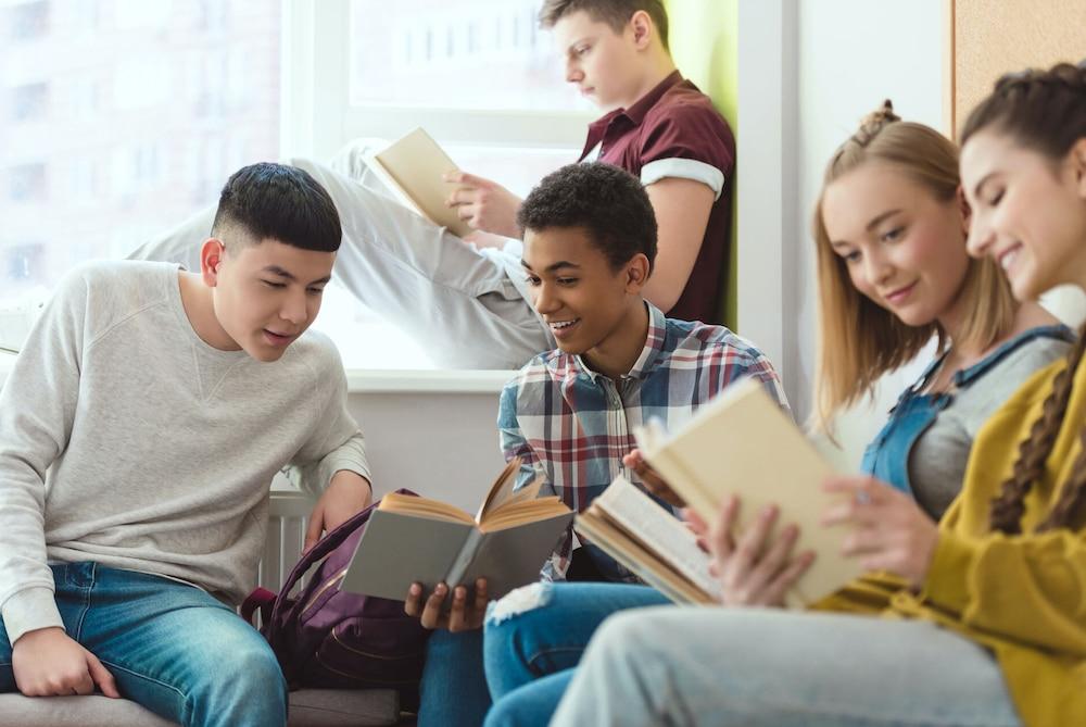 Fünf Jugendliche sitzen zusammen, lesen in Büchern und tauschen sich teilweise darüber aus.