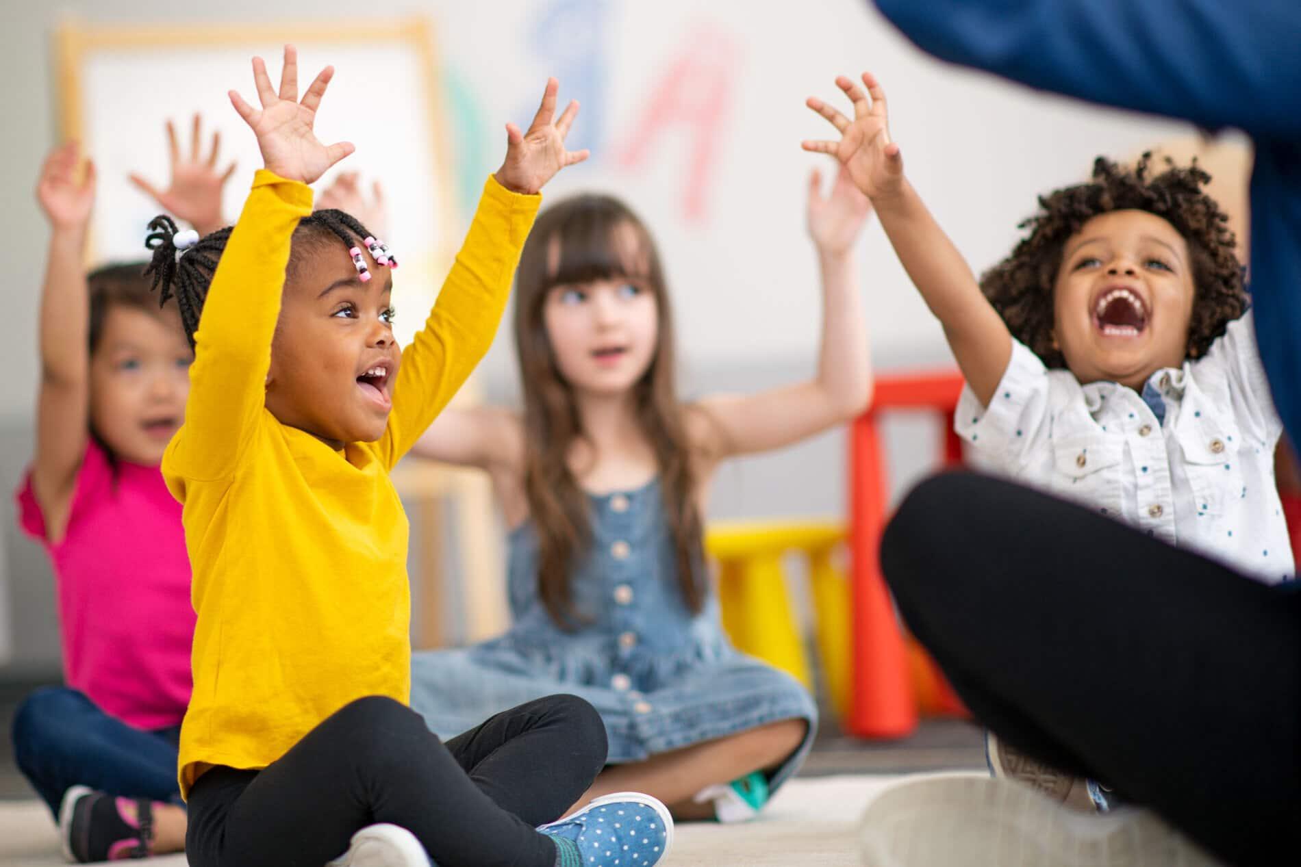 Kleinkinder werden von einer erwachsenen Person animiert, die Hände hoch zu halten, und lachen dabei.